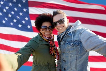 julio: personas, la amistad internacional y el concepto de la tecnología - feliz pareja adolescente toma autofoto internacional sobre el fondo de la bandera