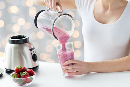 food concept: healthy eating, cooking, vegetarian food, dieting and people concept - close up of woman with blender and strawberries pouring milk shake to glass over holidays lights background Stock Photo