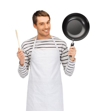 delantal: personas, cocina y concepto culinario - hombre feliz o cocinero en el delantal con el sartén y cuchara de madera Foto de archivo