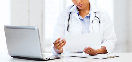 looking at computer: healthcare, medical and technology concept - african female doctor with laptop pc writing prescription