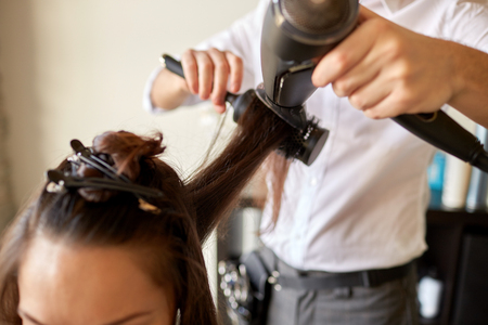 hairdressing: beauty, hairstyle, blow-dry and people concept - close up of young woman and hairdresser with fan and brush making hot styling at hair salon Stock Photo
