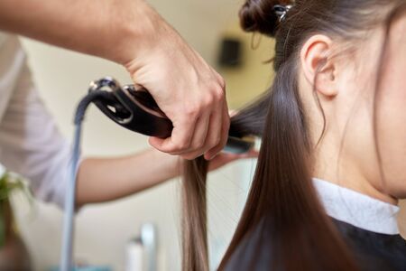 strand of hair: beauty, hairstyle, hot styling and people concept - close up of stylist hands with styling iron straightening woman hair at salon