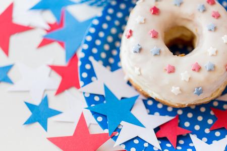 julio: día de la independencia americana, celebración, el patriotismo y el concepto de vacaciones - cerca de buñuelo dulce esmaltado con la decoración de las estrellas en el plato desechable en el 4º partido de julio de arriba Foto de archivo