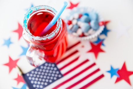 day dream: american independence day, celebration, patriotism and holidays concept - close up of juice glass, flag and candies at 4th july party