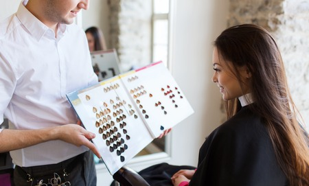 color hair: beauty, hair dyeing and people concept - happy young woman with hairdresser choosing hair color from palette samples at salon Stock Photo