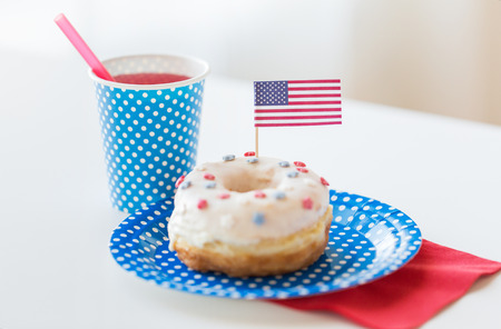 american independence day, celebration, patriotism and holidays concept - close up of glazed sweet donut decorated with flag and juice in disposable tableware at 4th july party Stock Photo