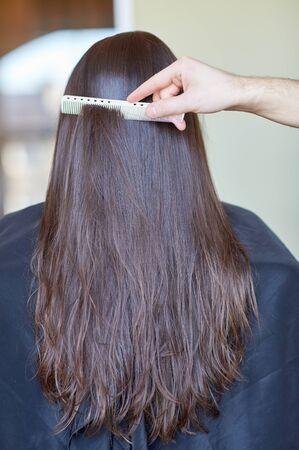 mujeres de espalda: belleza, cuidado del cabello, el peinado y el concepto de la gente - la mano del estilista con peine peinado del cabello de la mujer en el salón Foto de archivo