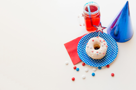 food state: american independence day, celebration, patriotism and holidays concept - close up of glazed sweet donut decorated with star, juice in glass mason jar or mug and candies at 4th july party from top