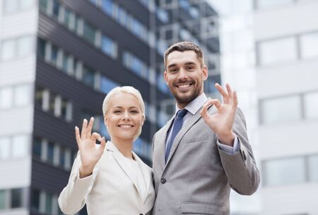 co workers: business, partnership, gesture success and people concept - smiling businessman and businesswoman making ok gesture over office building