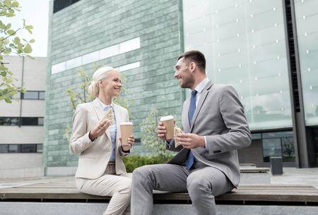 negocios comida: negocios, asociación, alimentos, bebidas y concepto de la gente - hombres de negocios sonriente con los vasos de papel que se coloca sobre el edificio de oficinas Foto de archivo