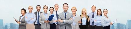 negocios, personas, corporativo, trabajo en equipo y el concepto de Oficina - grupo de empresarios felices sobre el fondo de la ciudad