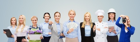group of workers: people, profession, employment, compensation and finances concept - happy businesswoman holding dollar money with group of professional workers over blue background