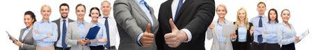 het bedrijfsleven, mensen, samenwerking, succes en gebaar concept - zakenman en zakenvrouw blijkt thumbs up over groep van office team achtergrond Stockfoto