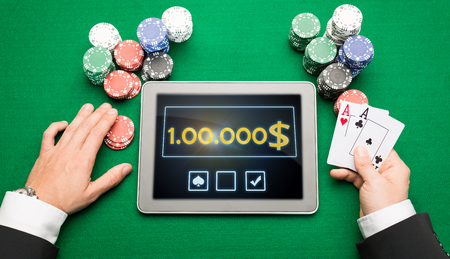 texas hold em: casino, online gambling, technology and people concept - close up of poker player with playing cards, tablet pc computer and chips at green casino table Stock Photo
