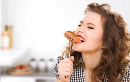 over eating: people, diet, culinary and food concept - hungry young woman eating meat on fork over kitchen background Stock Photo