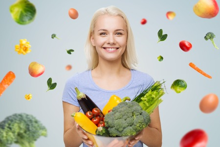 healthy eating, vegetarian food, dieting and people concept - smiling young woman with bowl of vegetables over gray background with falling vegetables