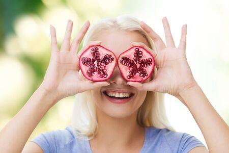 frutas divertidas: alimentación saludable, alimentos orgánicos, la dieta de frutas, el concepto de cómic y la gente - mujer feliz que se divierten y que cubre sus ojos con la granada sobre fondo verde natural Foto de archivo