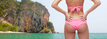 people, fashion, swimwear, summer beach and beauty concept - close up of young woman buttocks in pink bikini over sea and rock background