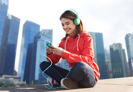 personas escuchando: la tecnolog�a, los viajes, el turismo y la gente concepto - mujer joven o adolescente con el tel�fono inteligente y los auriculares escucha la m�sica sobre fondo de la ciudad de Singapur sonriendo