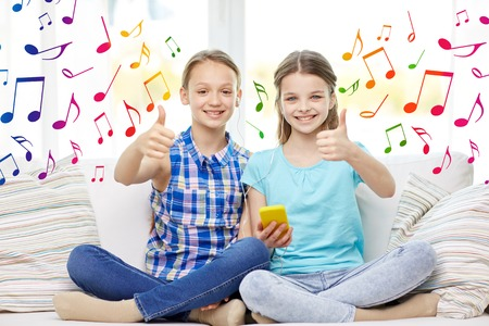 note: people, children, technology, friends and friendship concept - happy little girls with smartphone and earphones listening to music and showing thumbs up at home over colorful musical notes background Stock Photo