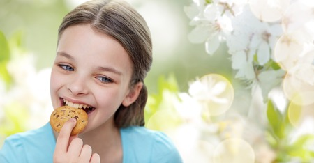 pre teen girls: people, happy childhood, food, sweets and bakery concept - smiling little girl eating cookie or biscuit over green natural background