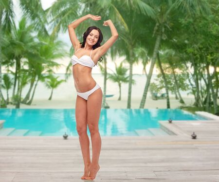 tiptoe: people, fashion, swimwear, summer and beach concept - happy young woman posing in white bikini swimsuit with raised hands over swimming pool at beach resort