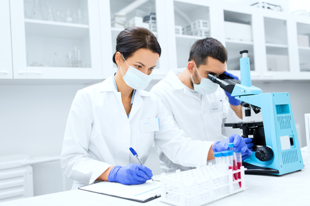 clinical: science, chemistry, technology, biology and people concept - young scientists with test tube and microscope making research in clinical laboratory and taking notes