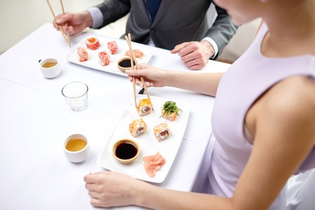 asia people: restaurant, food, people, date and holiday concept - close up of couple eating sushi at restaurant
