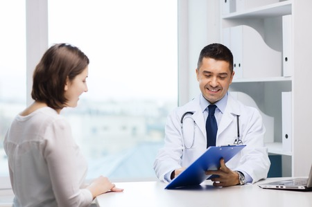 medicine, health care and people concept - smiling doctor with clipboard and young woman meeting at hospital