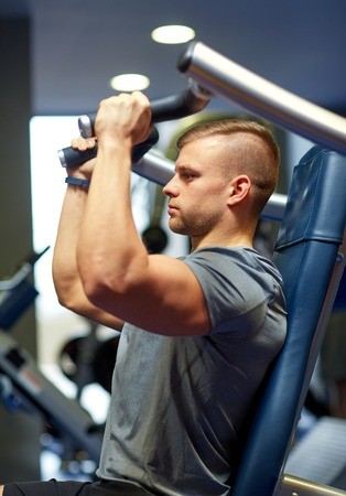 warm up: sport, fitness, bodybuilding, lifestyle and people concept - man exercising and flexing muscles on gym machine Stock Photo