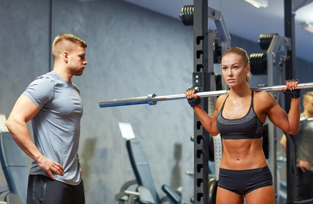 Weights: sport, fitness, bodybuilding, lifestyle and people concept - man and woman with barbell flexing muscles in gym Stock Photo