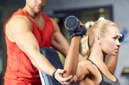 personal trainer: sport, fitness, bodybuilding, lifestyle and people concept - man and woman with dumbbells flexing muscles in gym