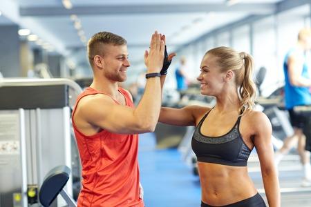 фитнес: спорт, фитнес, образ жизни, жест и люди концепции - улыбается мужчина и женщина делает высокие пять в тренажерном зале