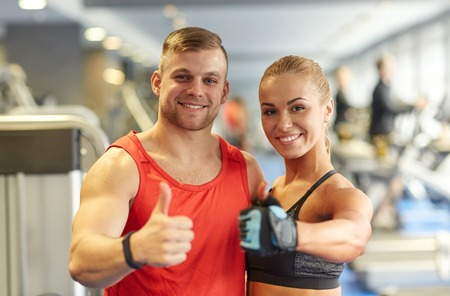 trainer: sport, fitness, lifestyle, gesture and people concept - smiling man and woman showing thumbs up in gym Stock Photo