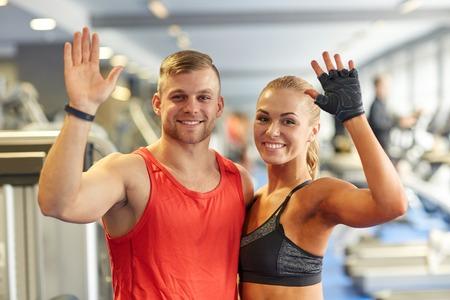 sport, fitness, lifestyle, gebaar en mensen concept - lachende man en vrouw wuivende handen in de sportschool Stockfoto