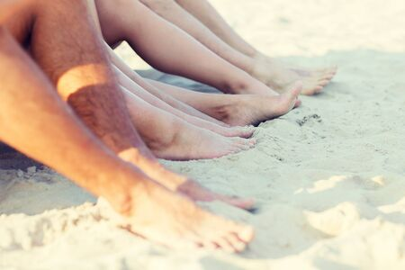 young boys: friendship, happiness, summer vacation, holidays and people concept - close up of friends sitting beach Stock Photo