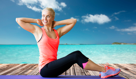 situp: fitness, sport, exercising and people concept - smiling woman doing sit-up on mat over sea and wooden berth at resort background Stock Photo