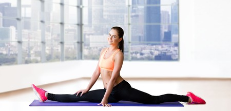sit up: fitness, sport, exercising, stretching and people concept - smiling woman doing splits on mat over gym background