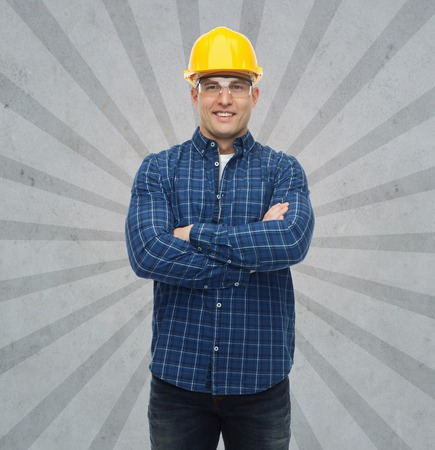 protective: repair, construction, building, people and maintenance concept - smiling male builder or manual worker in helmet over gray burst rays background Stock Photo