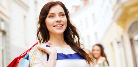 femal: shopping and tourism concept - beautiful woman with shopping bags in ctiy Stock Photo