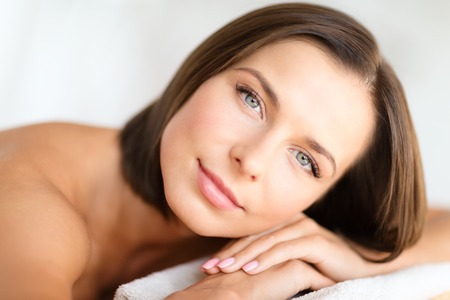 skin care: health, beauty, resort and relaxation concept - beautiful woman in spa salon lying on the massage desk
