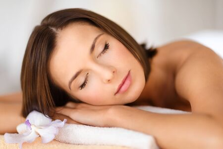 beauty resort: health, beauty, resort and relaxation concept - beautiful woman in spa salon lying on the massage desk