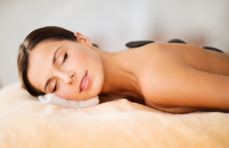 hot stones: health and beauty, resort and relaxation concept - beautiful woman with closed eyes in spa salon with hot stones