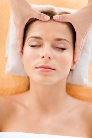 treatment: health, beauty, resort and relaxation concept - beautiful woman in spa salon getting face treatment Stock Photo