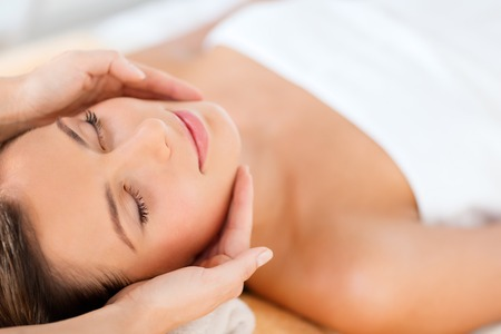 health, beauty, resort and relaxation concept - beautiful woman in spa salon getting face treatment Stock Photo