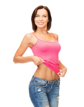 health, diet and beauty concept - happy woman taking off blank pink tank top or showing abs