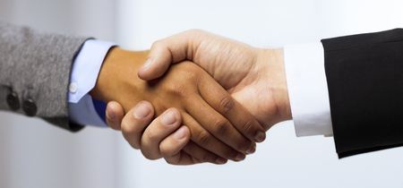 handshake: business and office concept - businessman and businesswoman showing shaking hands in office Stock Photo