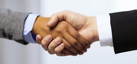 zakelijke en office concept - zakenman en zakenvrouw met handen schudden in het kantoor