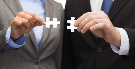 linking together: business concept - businessman and businesswoman trying to connect puzzle pieces in office Stock Photo
