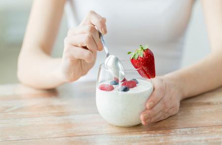 eten: gezond eten, vegetarisch eten, dieet en mensen concept - close-up van de handen van de vrouw met yoghurt en bessen op tafel